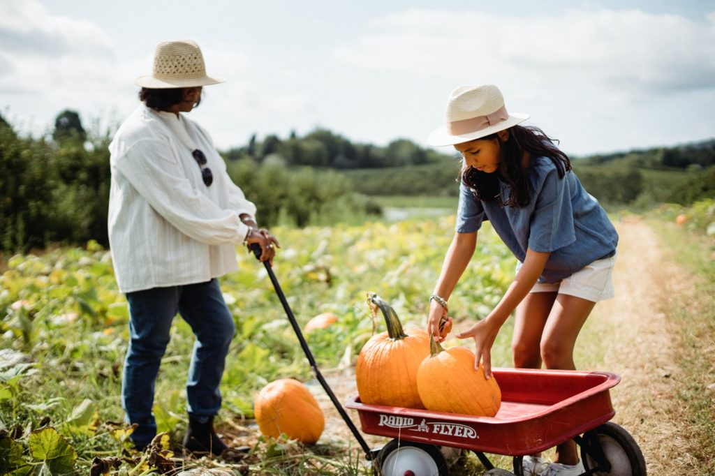 woman with daughter in field with pumpkins