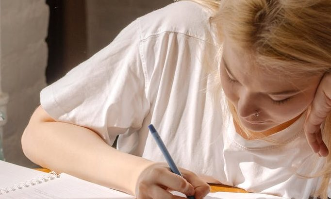 woman in white shirt writing on white paper