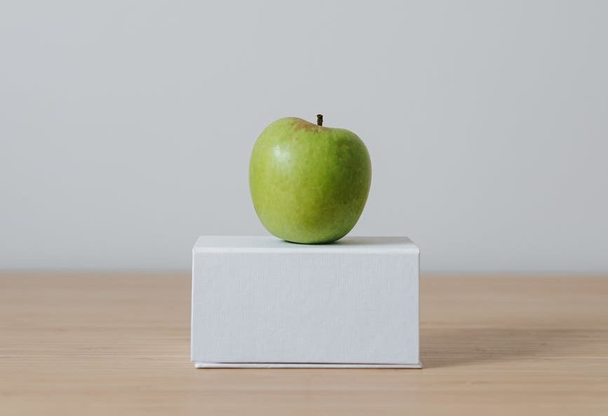 green apple on cardboard box on white background