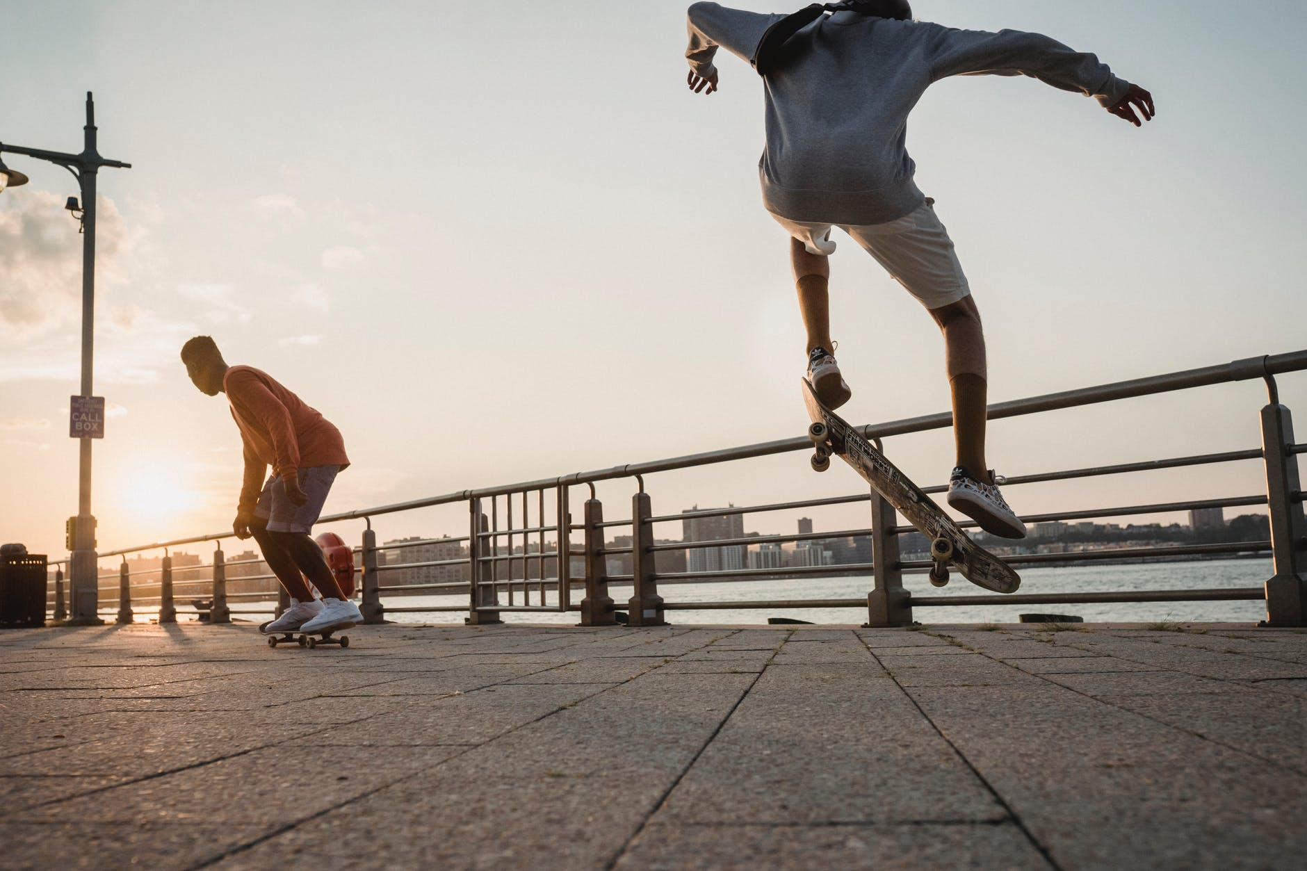 unrecognizable male skaters performing tricks on embankment in evening