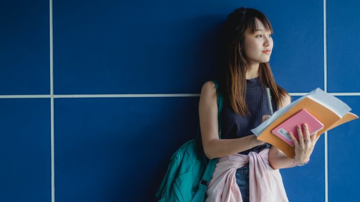 contemplative asian student with copybooks near tiled wall