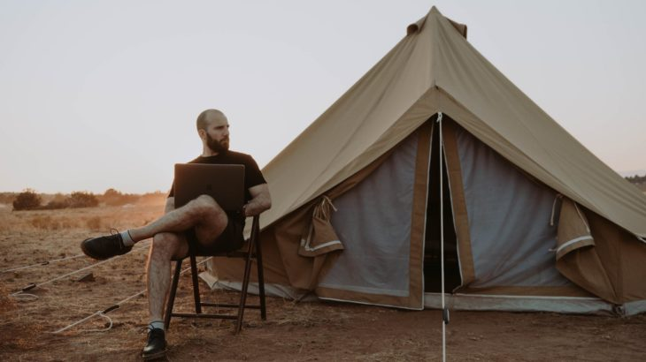 man relaxing with laptop near tent