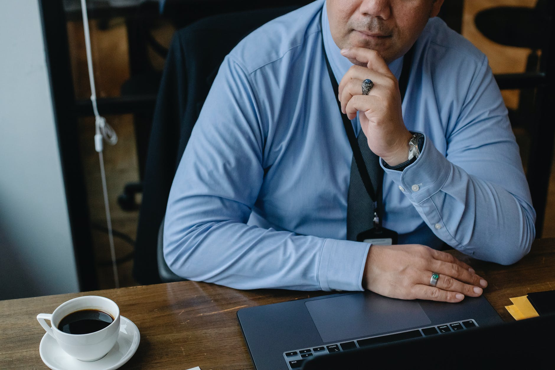 serious businessman touching chin while working on laptop