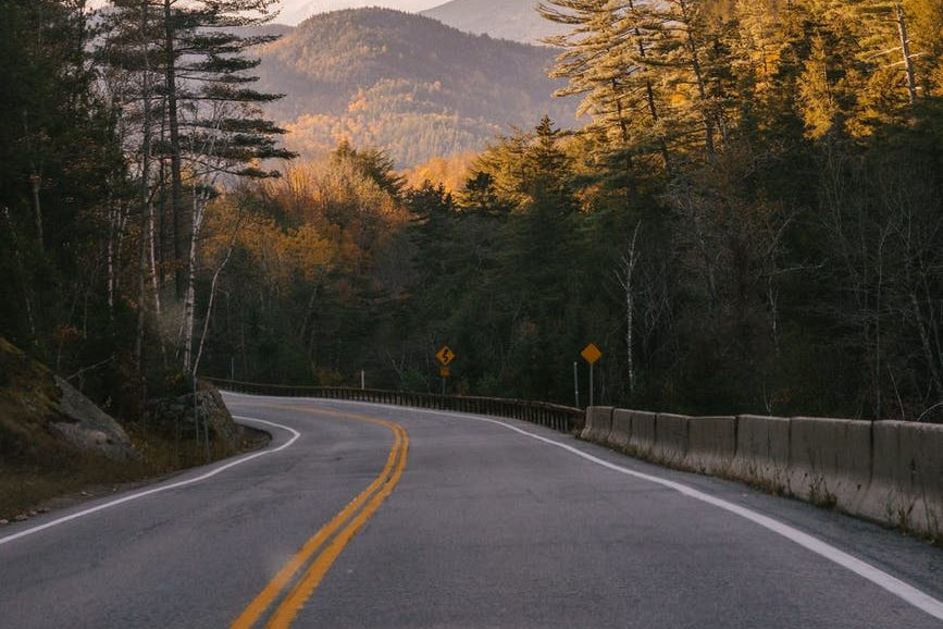 car driving on asphalt road among mountains covered with lush forests