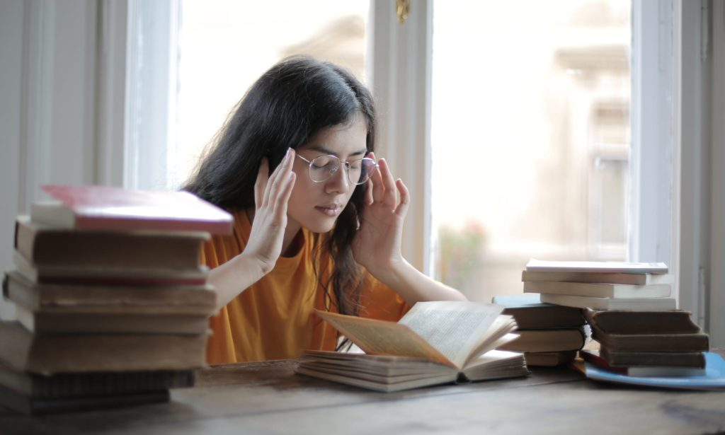 female student suffering from headache in library