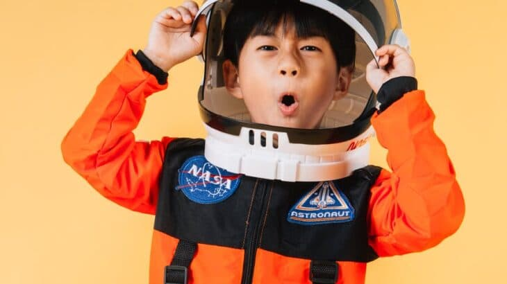 expressive asian boy putting on spaceman helmet