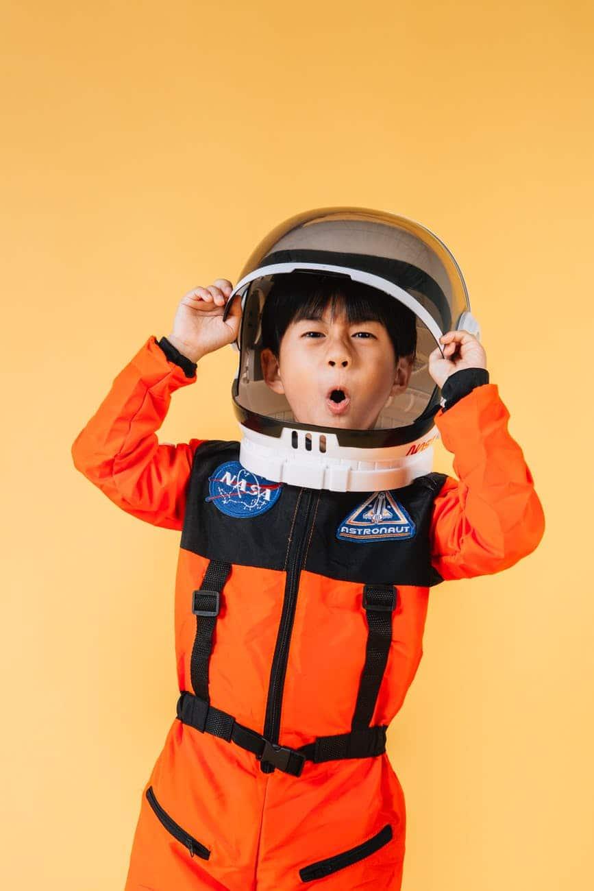 expressive asian boy putting on spaceman helmet